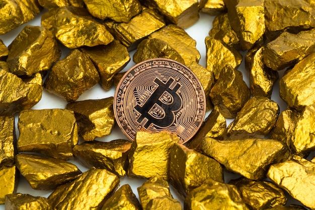 Close up da moeda digital de bitcoin e pepita de ouro sobre fundo branco