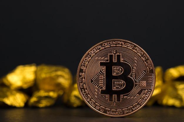 Close up da moeda digital do bitcoin e da pepita de ouro no fundo preto,