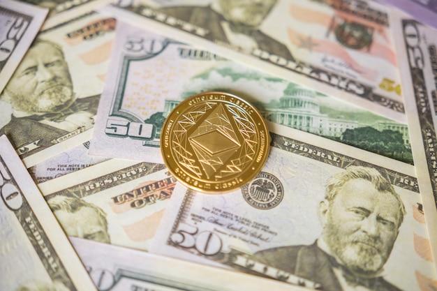 Close-up da moeda etherium de ouro em dólares americanos. conceito de negócio de criptomoeda.