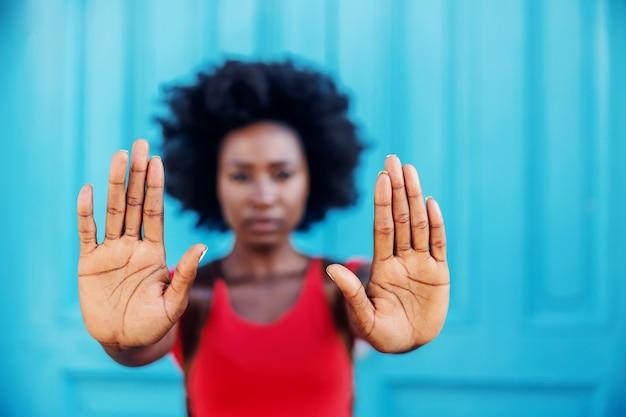 Close-up da mulher africana, de mãos dadas como um sinal de stop.