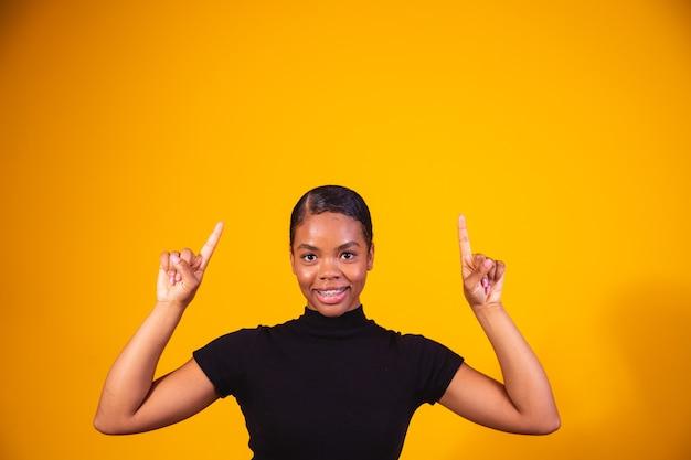 Close-up da mulher afro sorrindo sobre fundo amarelo, apontando para cima no espaço para o texto.
