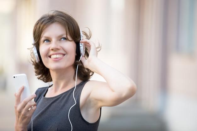 Close-up da mulher alegre ouvir música