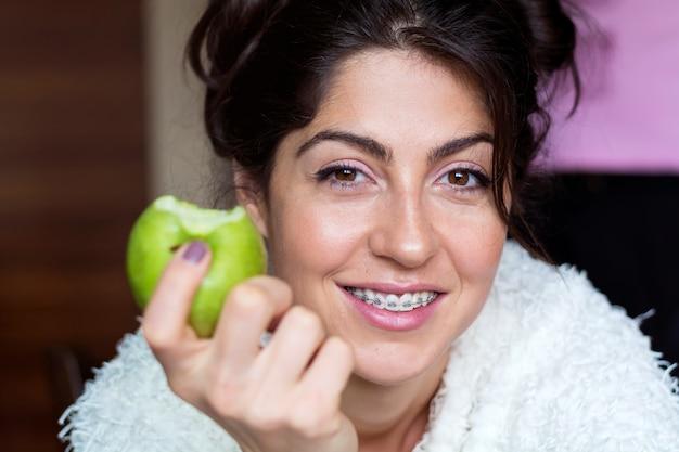 Close-up da mulher alegre que come uma maçã
