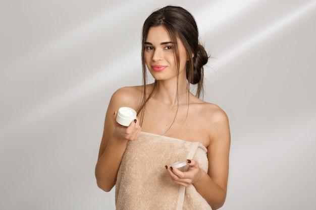 Close up da mulher alegre, segurando o pote de creme aberto, olhando em linha reta.