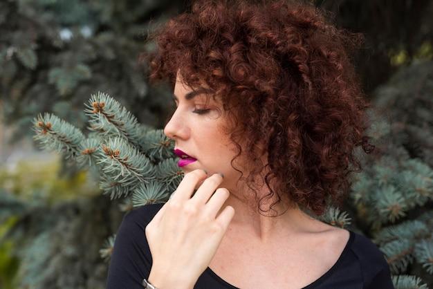 Close-up da mulher ao lado da árvore
