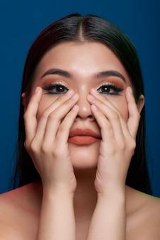 Close-up da mulher asiática com maquiagem pesada e mãos cobrindo as bochechas, olhando para a câmera