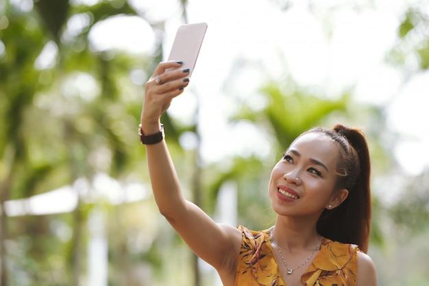 Close-up da mulher asiática elegante feliz com rabo de cavalo e maquiagem tomando selfie com smartphone