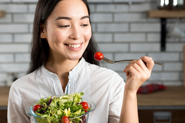 Close-up da mulher asiática feliz comendo salada saudável