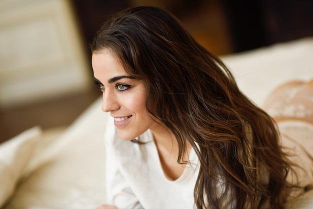 Close-up da mulher atrativa de cabelos compridos na cama