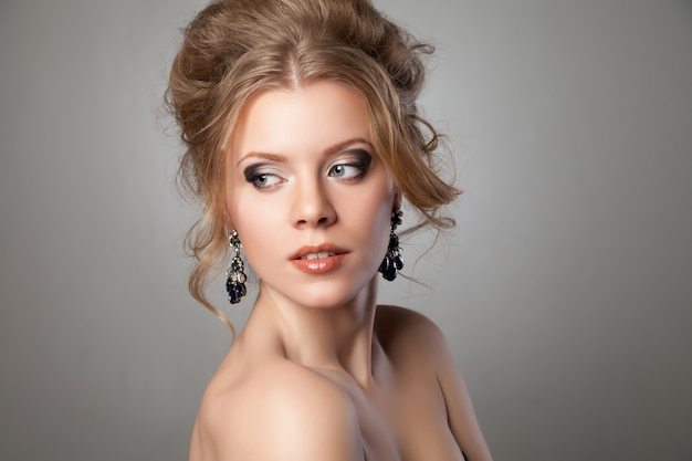 Close-up da mulher bonita com maquiagem de noite e brincos pretos grandes. joias e beleza. foto de moda