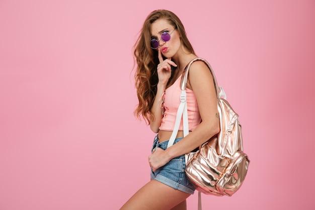 Close-up da mulher bonita jovem pensando readhead com mochila metálica