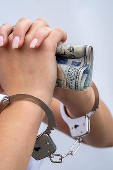 Close-up da mulher com as mãos algemadas, segurando o dólar. suborno e corrupção