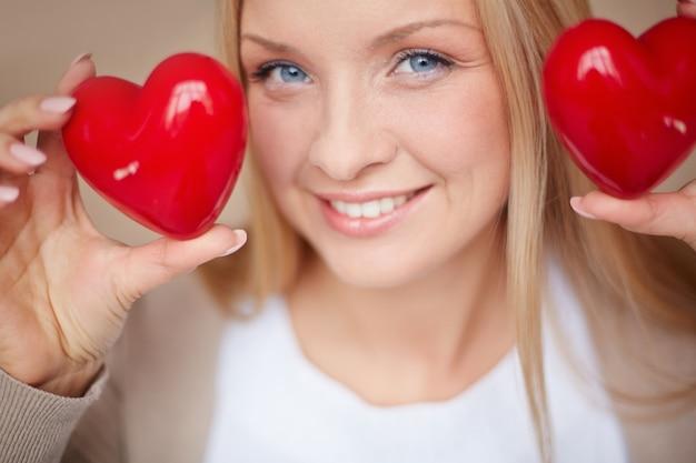 Close-up da mulher com dois corações vermelhos