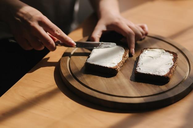 Close-up da mulher com manteiga no pão de centeio torrado com manteiga vegana. torrada de manteiga de mulher em casa em madeira
