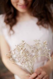 Close-up da mulher com uma flor silvestre