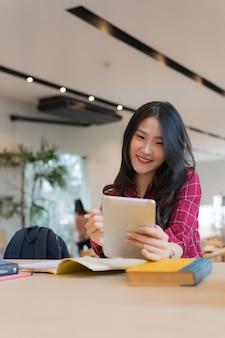 Close-up da mulher de negócios jovem grande sorrindo de orelha a orelha, mantendo o tablet na mão na mesa, conceito de sucesso