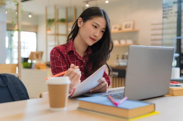 Close-up da mulher de negócios jovem sentado segurando a caneta e o caderno laranja nas mãos na mesa e assistindo o notebook
