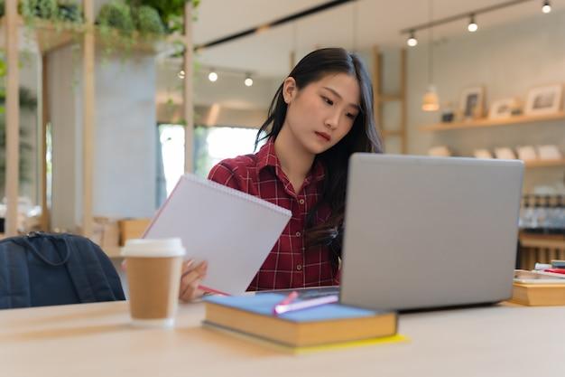 Close-up da mulher de negócios jovem sentado segurando o notebook na mão na mesa e assistindo notebook