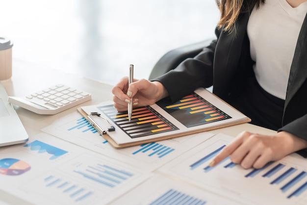 Close-up da mulher de negócios trabalhando mão apontando gráfico no escritório.