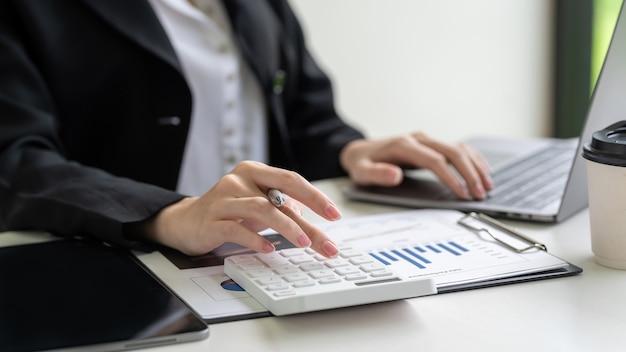 Close-up da mulher de negócios usando a calculadora para fazer cálculos contábeis com laptop e gráficos no escritório.