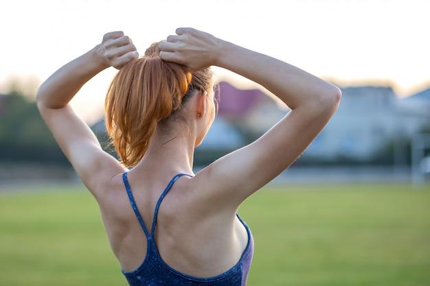 Close up da mulher desportiva de yong com o cabelo vermelho que está ao ar livre com braços levantados que aprecia o nascer do sol antes de treinar.