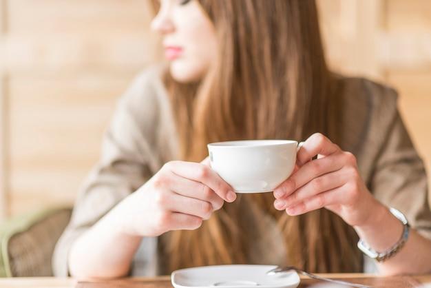 Close-up da mulher distraída com o copo de chá