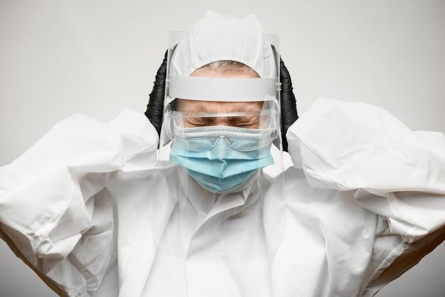 Close-up da mulher em traje de proteção com escudo e máscara médica que cobriu os ouvidos com as mãos.