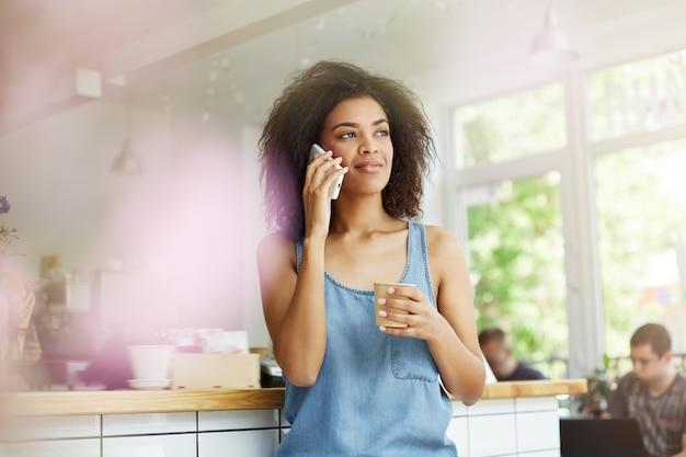 Close-up da mulher encantadora estudante de pele negra linda com cabelos crespos, sentado na cafeteria, bebendo café, falando no telefone com a mãe, contando sobre as realizações no estudo com sorriso no rosto