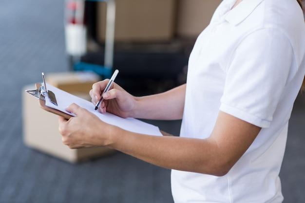 Close-up da mulher entrega está escrevendo sobre uma prancheta