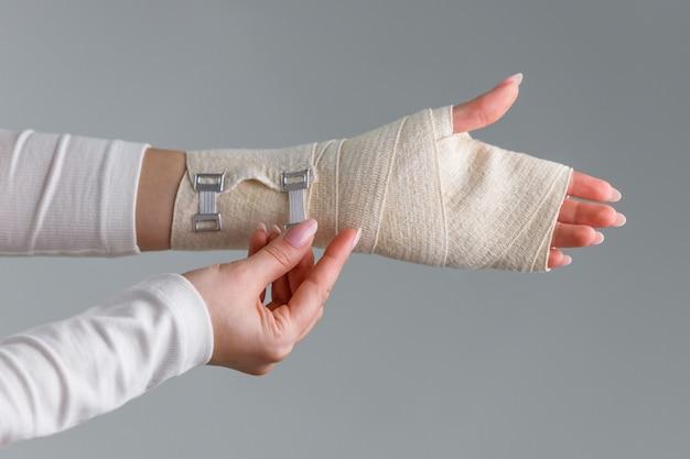 Close-up da mulher envolvendo seu pulso doloroso com bandagem ortopédica elástica flexível após esportes malsucedidos ou lesão