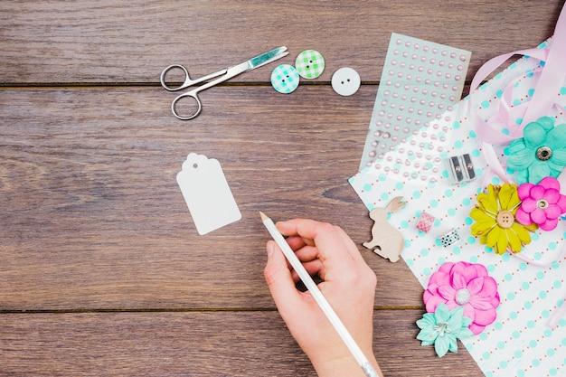 Close-up da mulher escrevendo na etiqueta branca com botões; flores; tesoura e artigos decorativos na mesa de madeira