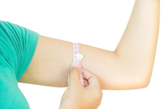 Close up da mulher está medindo o braço com fita métrica