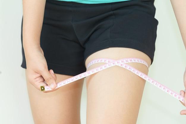 Close up da mulher está medindo sua coxa com fita métrica