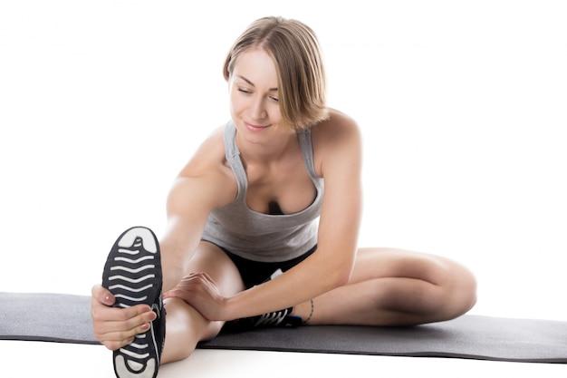 Close-up da mulher flexível sentado no tatame