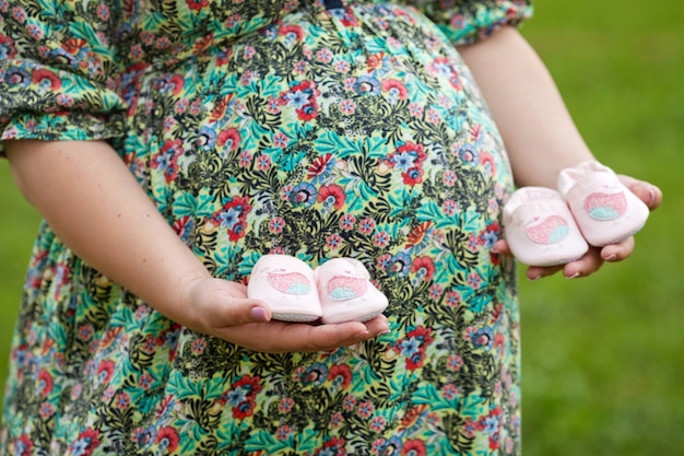 Close-up da mulher grávida segurando sapatos de bebê na barriga. gêmeos