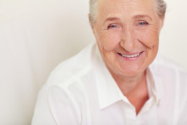 Close-up da mulher idosa com camisa branca