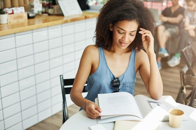 Close-up da mulher jovem e bonita encantadora estudante de pele escura com cabelos cacheados em roupa elegante, sentado no café após um longo dia na universidade, deinking café, fazendo a lição de casa com o rosto sutisfied ex
