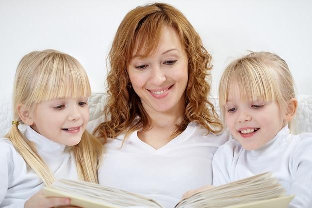 Close-up da mulher lendo com suas filhas