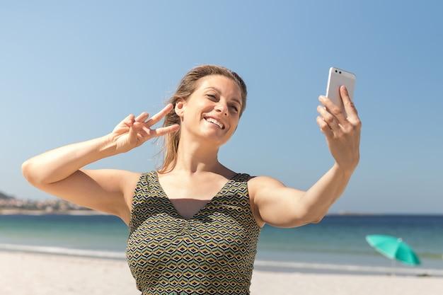 Close-up da mulher loira de meia-idade em um vestido verde, fazendo um selfie na praia.