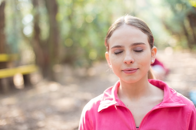 Close-up da mulher nova com a camisola rosa aprecia ao ar livre