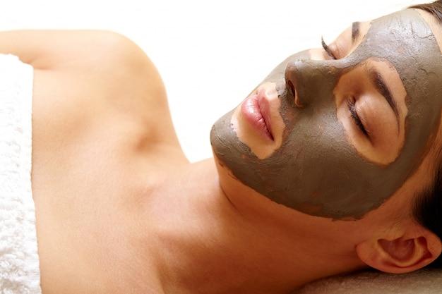 Close-up da mulher nova com máscara facial no rosto