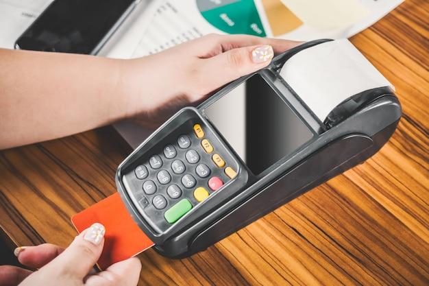Close-up da mulher que paga pelo cartão de crédito