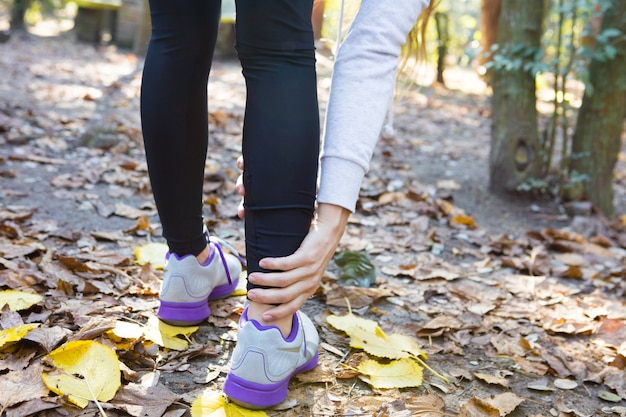 Close-up da mulher que toca em seu tornozelo direito