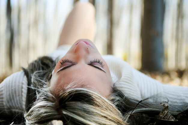 Close-up da mulher relaxado deitado sobre folhas