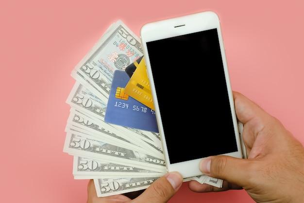 Close-up da mulher segurar dinheiro dólares americanos e usando cartão de crédito e telefone em branco na parede rosa. - conceito financeiro.