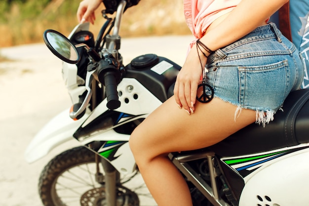 Close-up da mulher sentada em uma motocicleta em shorts