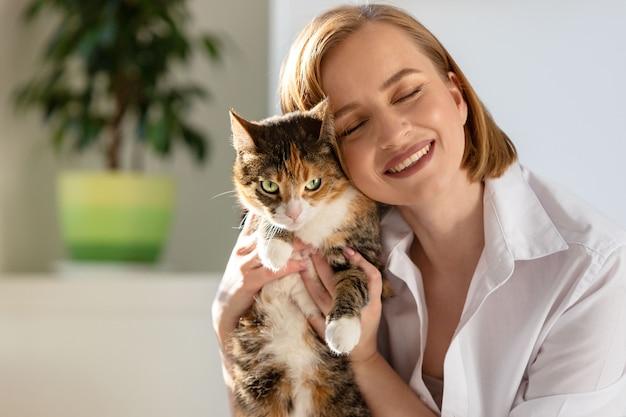 Close-up da mulher sorridente na camisa branca, abraçando e abraçando com ternura e amor gato doméstico em casa