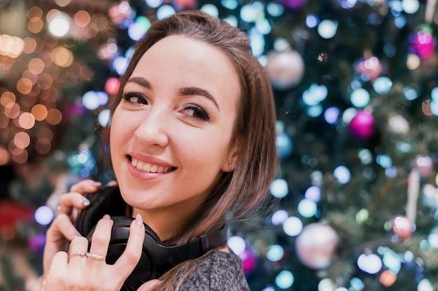 Close-up da mulher sorridente usando fones de ouvido perto da árvore de natal, olhando para longe