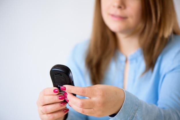 Close-up da mulher, verificando o nível de açúcar no sangue por glicosímetro em casa