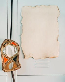 Close-up da página em branco queimada com máscara de olho de festa na porta do armário